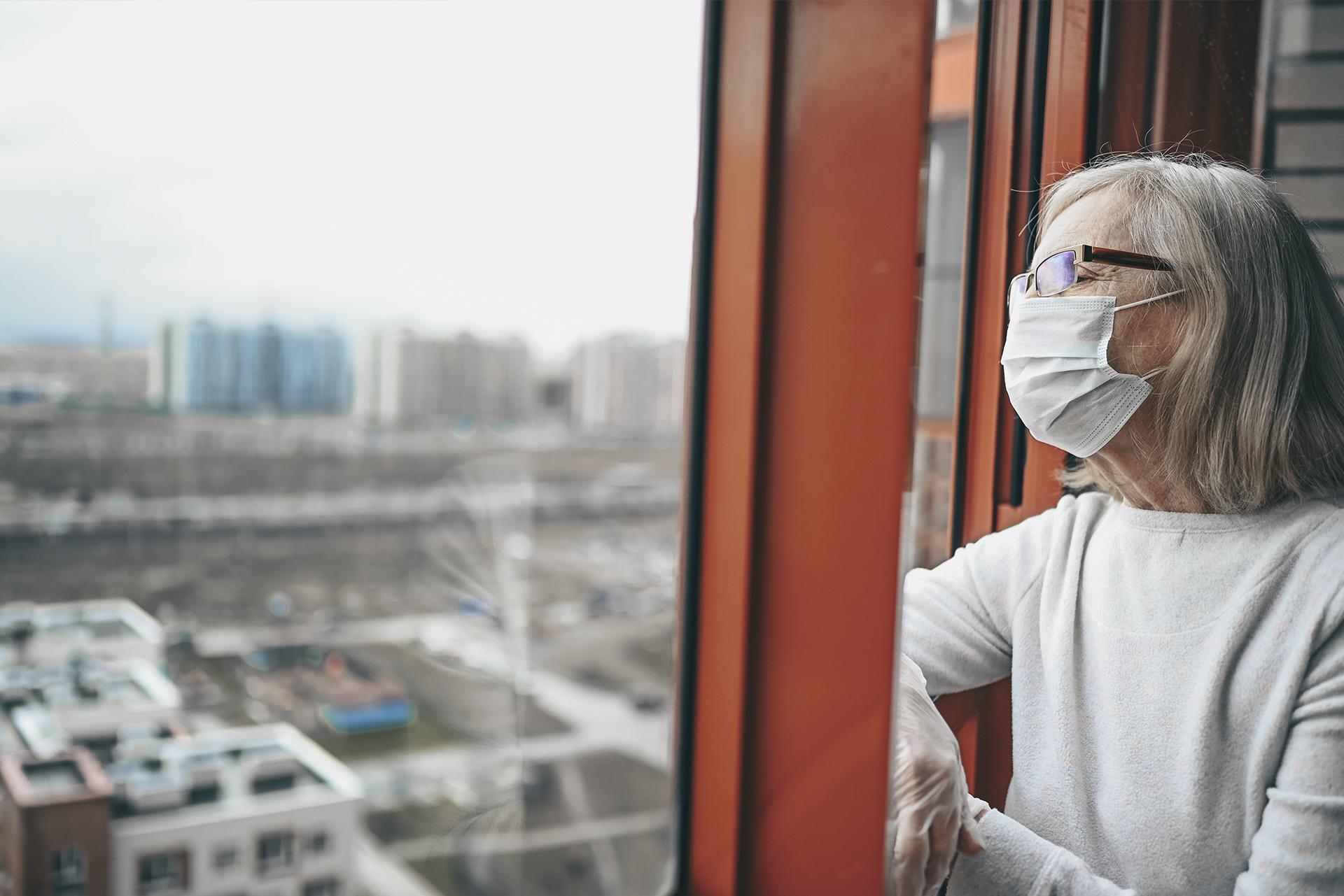 Mulher de máscara observando a janela