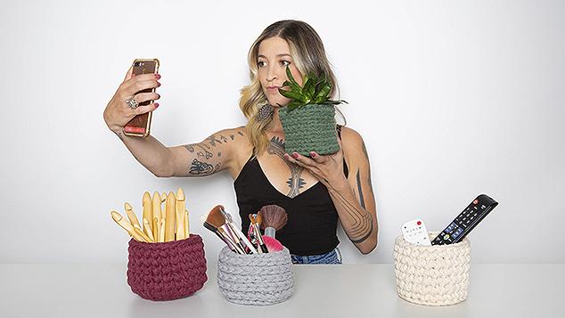Anne Galante fazendo selfie com vaso de plantas em crochê
